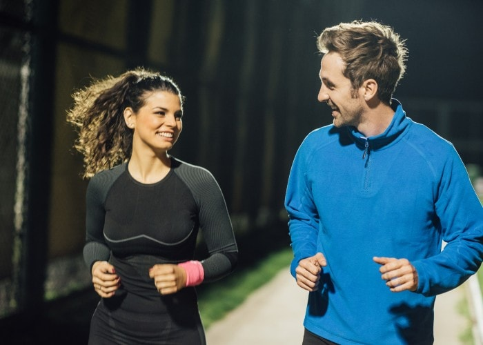 A smiling couple jogging under street lights in a park