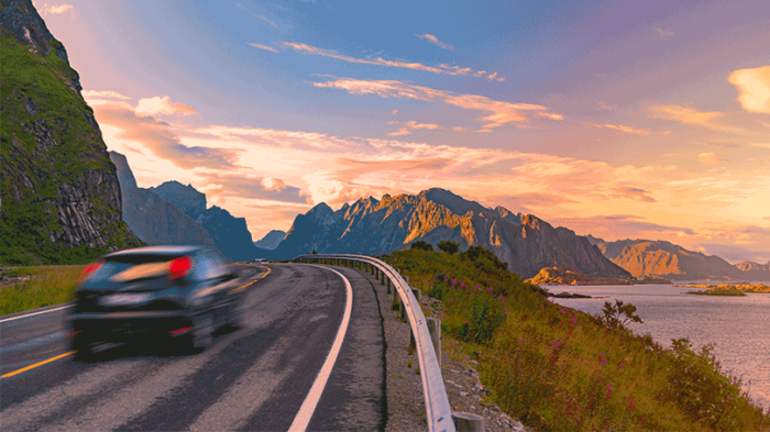 Car on scenic road by fjord in sunset