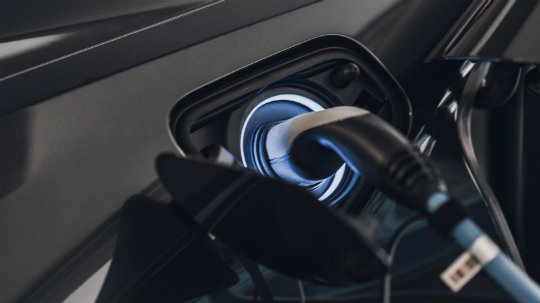 A charging cable plugged in to a car