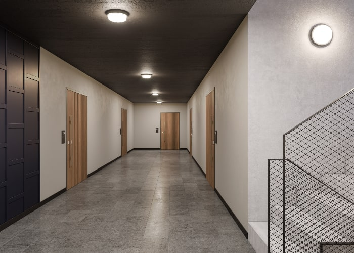 Protect in ceiling and on wall in wide, modern hallway