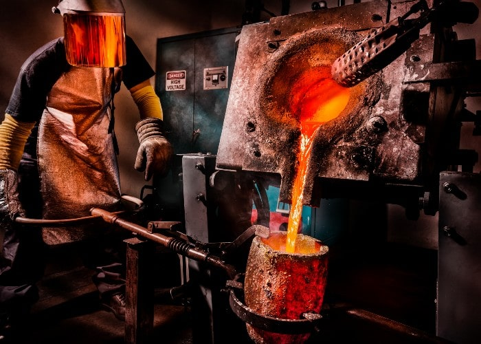 Man working with melted metal at foundry