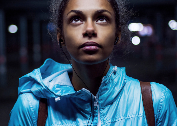 A young woman looking up at a street light