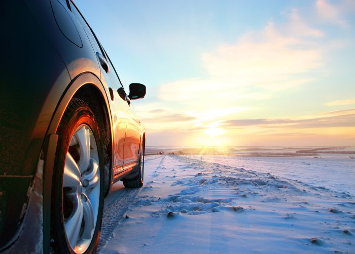 Car on winter road in sunrise