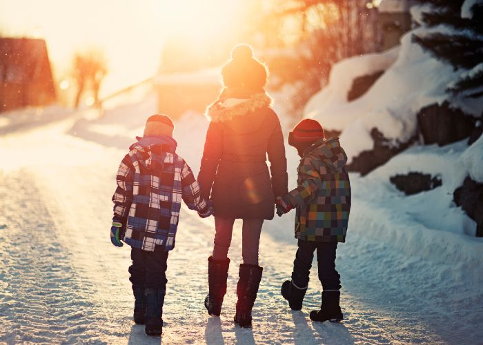 Children holding hands in sunset on winter road