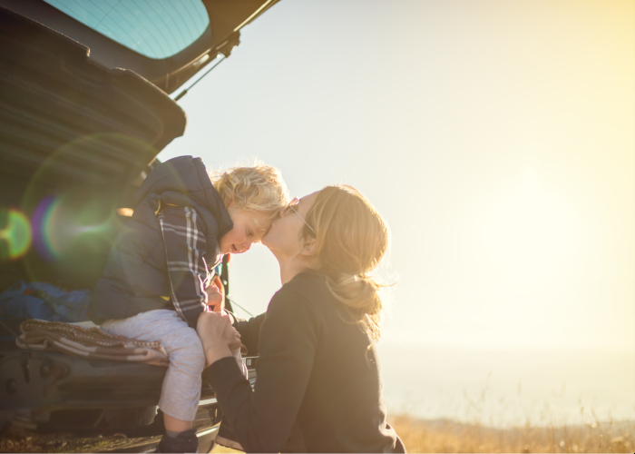 Woman kissing her son on the forehead winter car