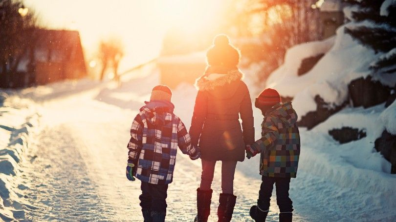 Three kids walking on a winter road