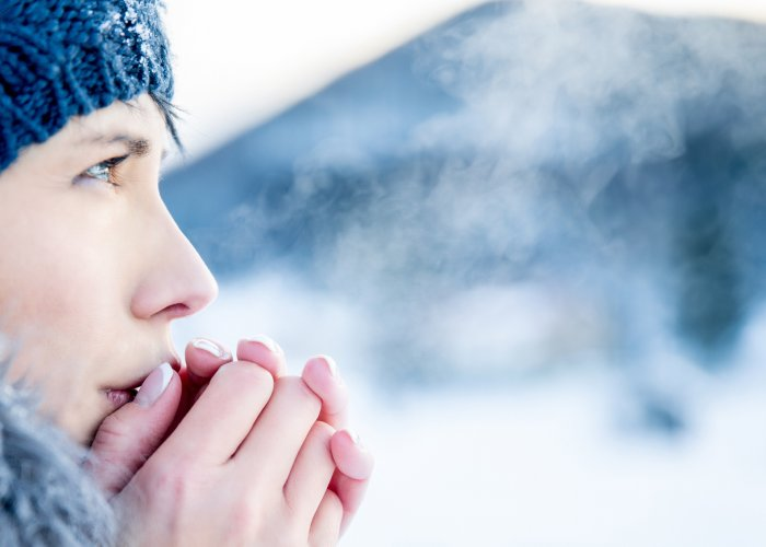 Woman breathing cloud in cold weather