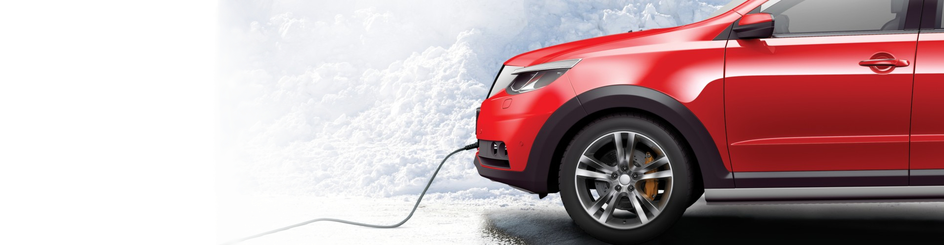 Red car in snowy landskape with green DEFA cable connected