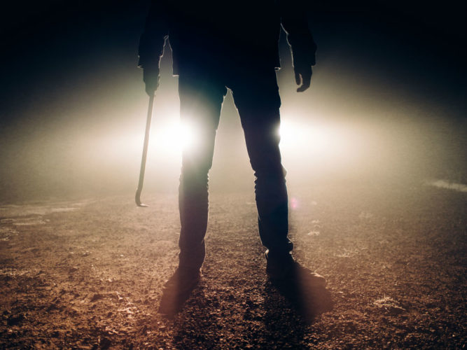 Dark silouette of a man holding a crowbar
